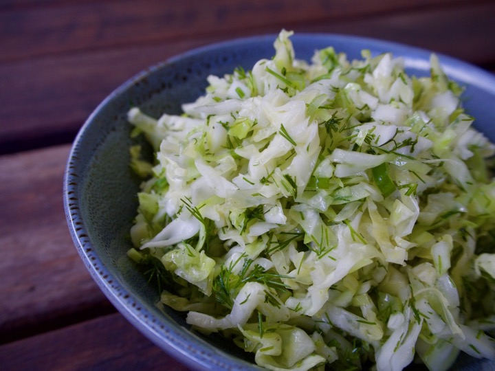 Young cabbage slaw with herbs on a blue plate