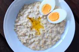 Oatmeal porridge on a white plate with butter and hard boiled eggs