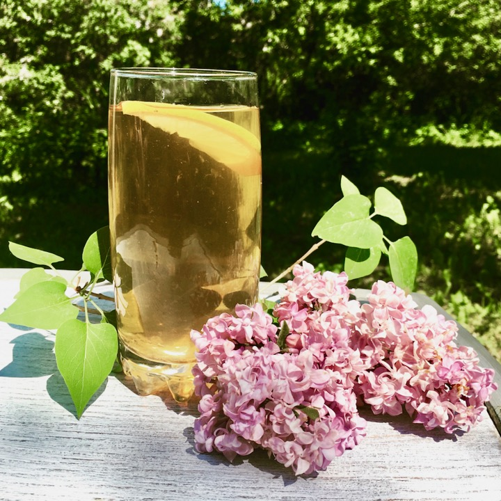 glass of ice tea on white chair with purple lilacs