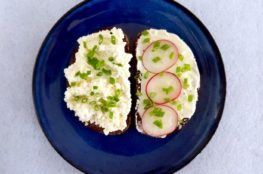 Rye bread open sandwich with cottage cheese and radishes on a blue plate