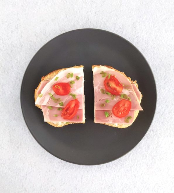 Open ham sandwich on white bread with tomato and chive garnish on grey plate and white background