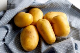 Yellow raw potatoes on a blue tea towel