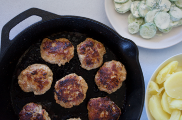 Latvian meatballs on a black cast iron pan with bowls of boiled potato and cucumber salad