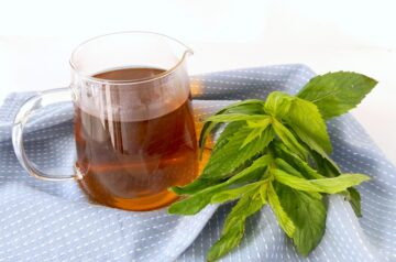 Mint tea jug on blue tea-towel background