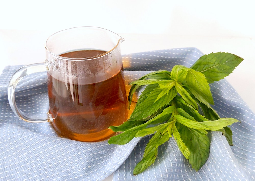 Mint tea jug on blue tea-towel background