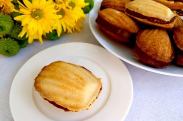 Madeleine shaped cookies with condensed milk caramel filling onawhite plate and yellow flavour background
