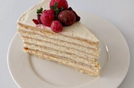 Honey cake on a white plate with red berry garnish