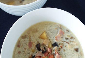 Mushroom soup in a shite bowl on dark background
